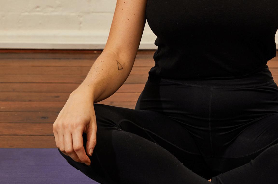 Close up of woman sitting in lotus pose.