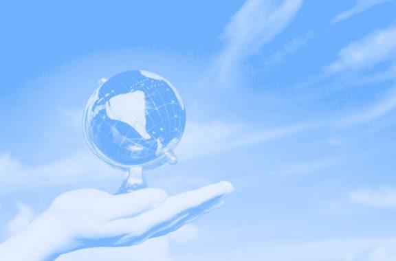 Blue washed feminine hand holding globe against a beautiful blue sky.