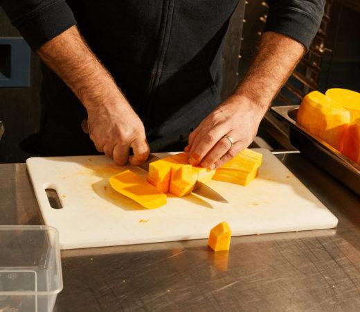 image of a man cutting pumpkin in a kitchen