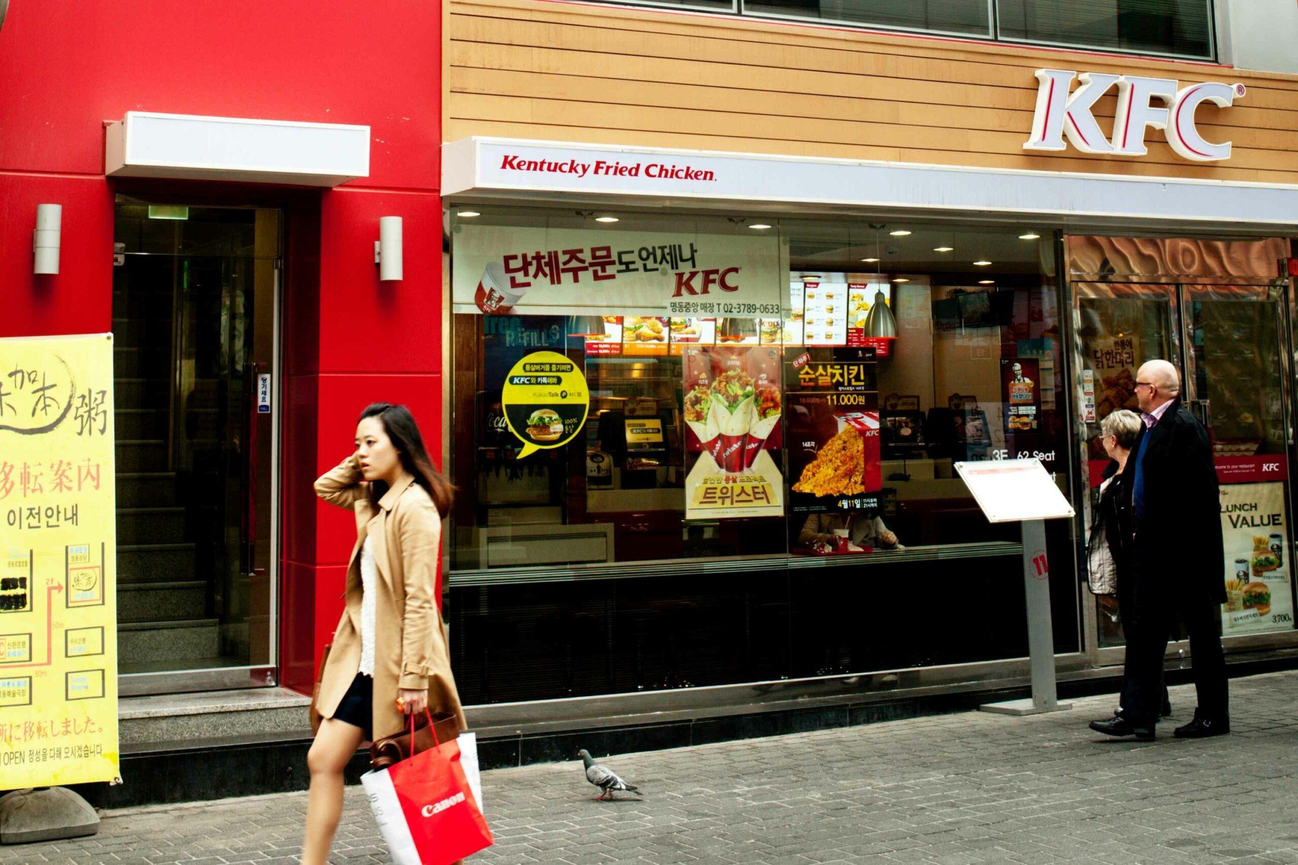 Woman walking past KFC store front