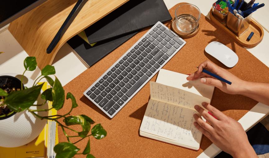 Hands resting on a desk flipping through notebook