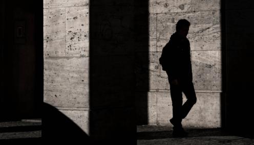 Shadow of man walking between buildings