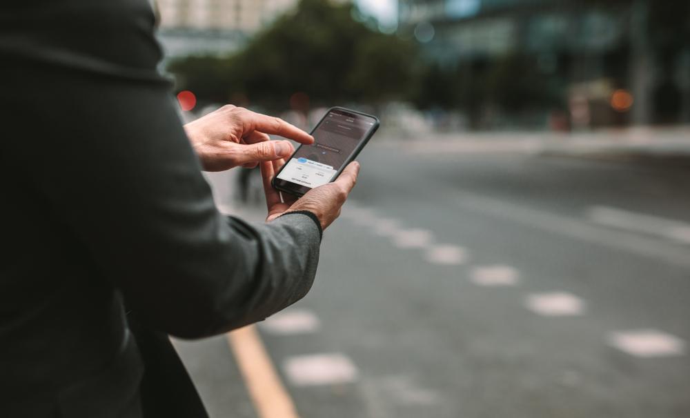 man holding smartphone finding rideshare