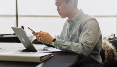 A man looking at his laptop looking at an HRIS